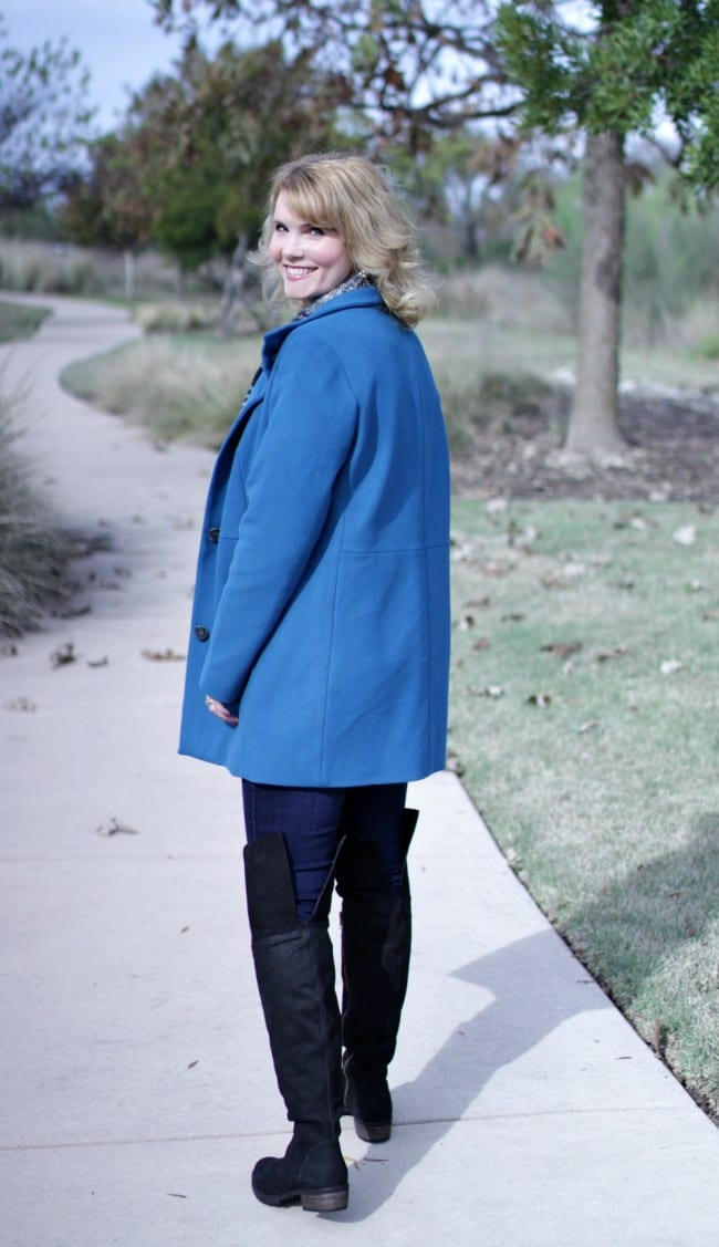 Women's winter coat in blue, paired with over the knee boots.
