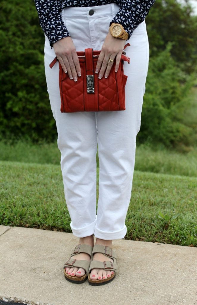 Spring fashion: White boyfriend jeans, Birkenstocks, button up shirt, orange handbag.