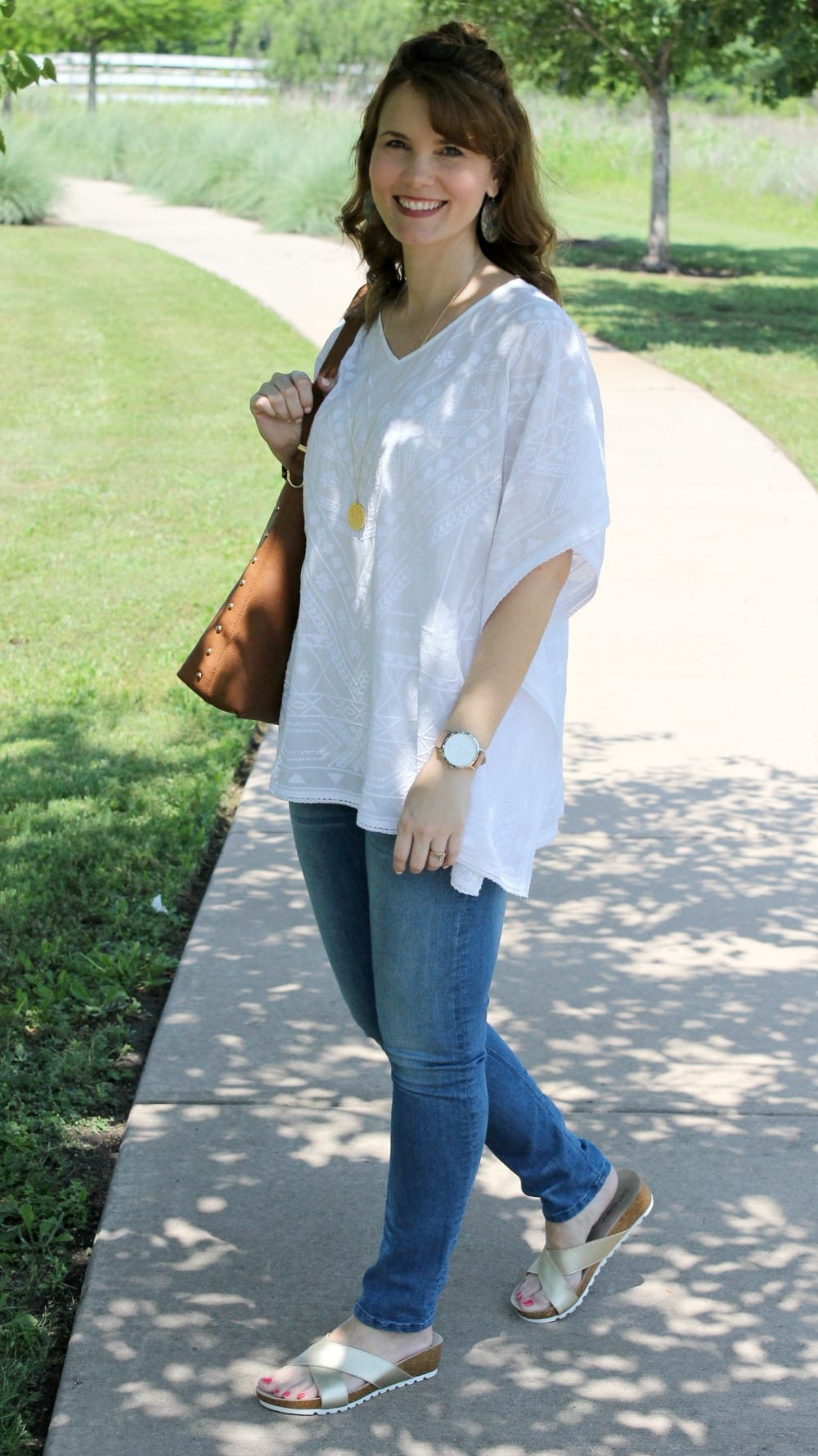 Casual spring outfit idea - White embroidered poncho, light denim, gold sandals from Secret Celebrity and a brown tassel handbag.