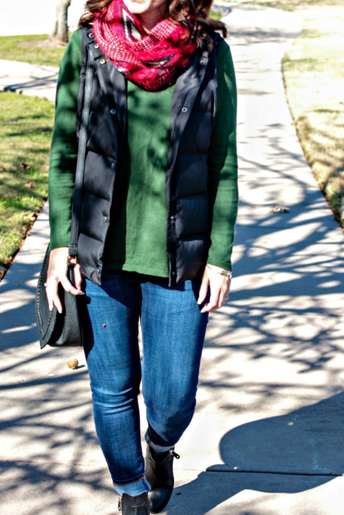A casual Holiday outfit idea - green sweater, puffer vest, denim, red scarf and ankle boots.