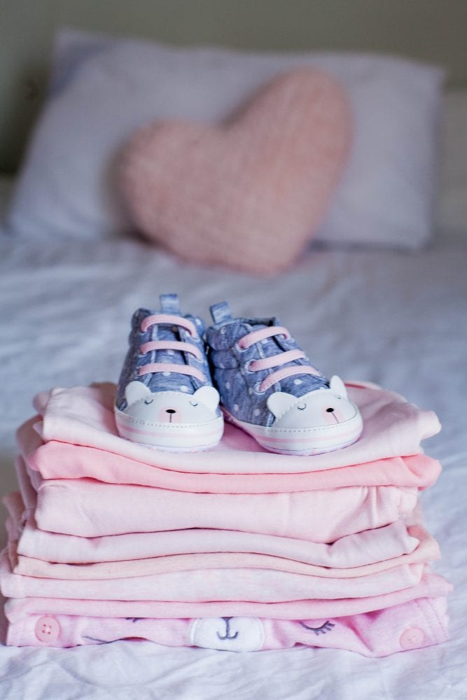 Children's Shoes And Clothes On The Bed. Beautiful Pink Baby Clo