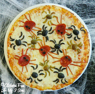 A cheese pizza decorated with pepperoni and olives in the shape of spiders