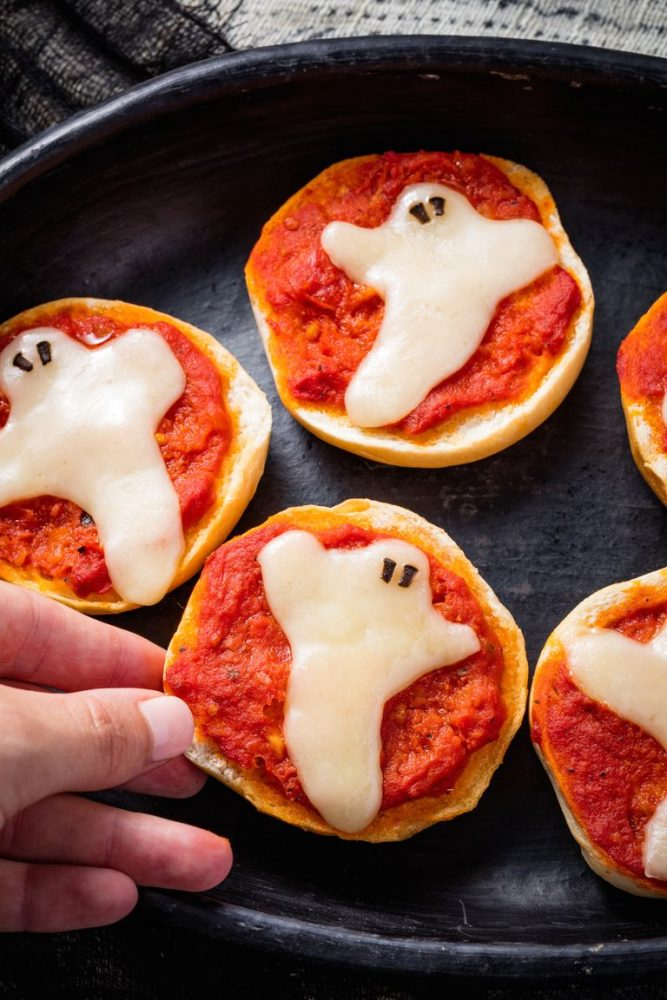 A bagel topped with tomato sauce and mozzarella cheese in the shape of a ghost.