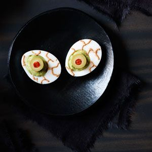 Hard boiled eggs with a pile of guacamole in place of the yolk, with an olive in the middle to look like a pupil, and red lines on the side to mimic a bloodshot eyeball.
