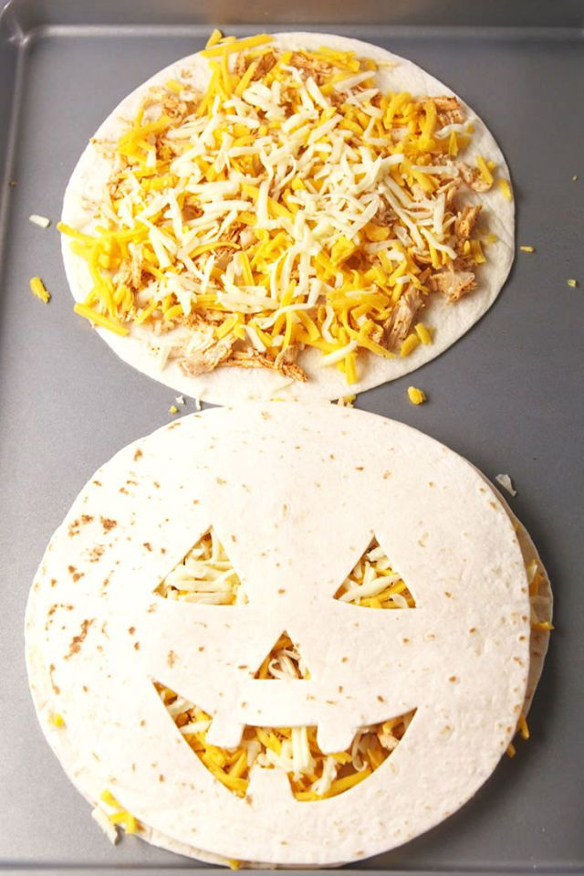 A quesadilla with a jack-o-lantern face cut out of the tortilla