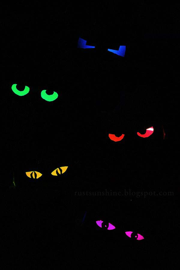Glow-in-the-dark Multi colored eyeballs, made by placing a glow stick inside of a toilet paper tube that has eye balls cut out of it